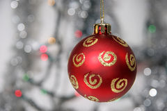 Red golden christmas ball against silvery background. And lights Royalty Free Stock Photography