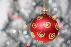 Red golden christmas ball against silvery background. And lights Royalty Free Stock Photos