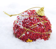 Red and golden christmas ball on the snow Royalty Free Stock Photo
