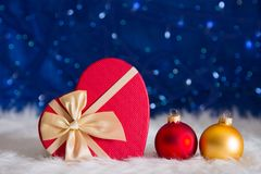 Red and golden Christmas balls with gift box in shape of heart o Royalty Free Stock Photo
