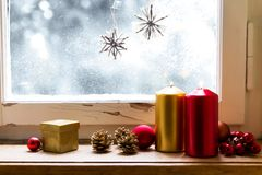 Christmas decoration on a window. Red and golden christmas decoration, indoors in front of a window Royalty Free Stock Photos
