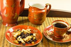 Red and Golden coffee pot, sugar bowl, and cup of coffee. Red and golden set of coffee served with raisins, walnuts and almonds, all over a rustic tray stock image