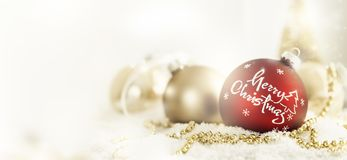 Red and golden balls for Christmas. Red and golden colored Christmas balls with greeting in artificial snow Royalty Free Stock Images