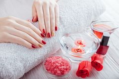 Red and golden manicure with spa essentials on white wooden table. Red and golden manicure design with spa essentials on white wooden table. Skin treatment Stock Image