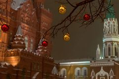 Red golden yellow ball on the tree Christmas decoration on the background of the Kremlin tower of Moscow and the historic. Museum in the evening light Royalty Free Stock Photography