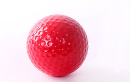 Red golf ball on red tee, white background Stock Photos