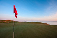 Red golf flag on a green at dawn. A red golf flag on a green in warm dawn light. Photo taken on the Castle Course in St Andrews, Scotland. Blue sky and the town royalty free stock image