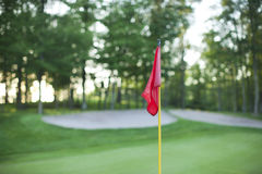 Red golf pin flag in front of defocused green Stock Photography