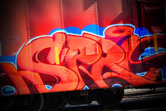 Red graffiti. A closeup view of talented red colorful graffit on side of a box cari Stock Image