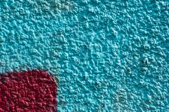 Red graffiti detail on a blue painted wall, facade. Abstract background, wallpaper. Exterior wall, facade stock photography