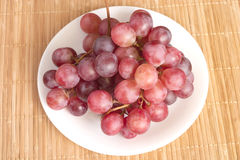 Red grape berries branch in white round plate Stock Photography