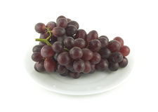 Red grape branch on plate isolated over white close up Royalty Free Stock Images