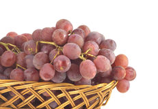 Red grape on branch in straw wicker basket isolate Stock Photography