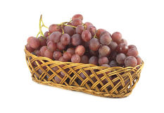Red grape on branch in straw wicker basket isolate Stock Photos