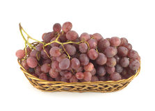 Red grape on branch in straw wicker basket isolate Royalty Free Stock Photo