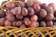Red grape branch in straw wicker basket isolated Royalty Free Stock Photography