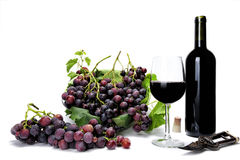 Red grape bunches and wine glass on white background. Stock Photo