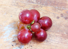 Red grape. Fresh red grape on wooden background Stock Image