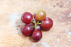 Red grape. Fresh red grape on wooden background Royalty Free Stock Images