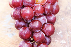 Red grape. Fresh red grape on wooden background Royalty Free Stock Photography