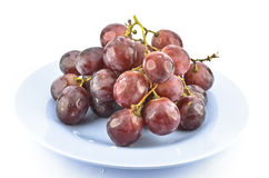 Red grape fruits on dish. On white background Royalty Free Stock Image