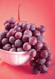 Red grape on pink. Fresh ripe red grape on pink background Royalty Free Stock Photo