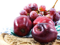 Red grape and red apples on tablecloth. Fresh red grape and red apples on tablecloth Royalty Free Stock Images