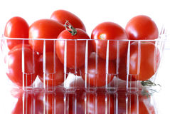 Red grape tomatoes packaged & reflecting. 0590. Ripe fresh grape tomatoes packaged in a clear ribbed container from the store. The vegetables are reflecting on a Royalty Free Stock Photography
