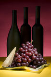 Red grape and wine bottle still life Stock Photos