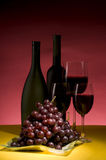 Red grape and wine bottle still life Royalty Free Stock Photography