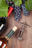 Red grape, wine bottles and corkscrew Royalty Free Stock Images
