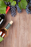 Red grape and wine bottles Stock Images