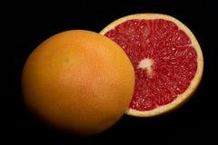 Red grapefruit. Halved ruby grapefruit on black background Stock Photography