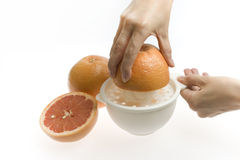 Red grapefruit being squeezed Royalty Free Stock Photo
