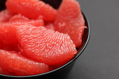 Red Grapefruit in a black bowl Stock Photo