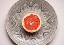Red grapefruit in grey plate Stock Image