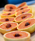 Red Grapefruit Halves with Grape Garnish Stock Photo