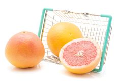 Red grapefruit isolated. Red grapefruits out a shopping basket isolated on white background two whole and one half Stock Photography