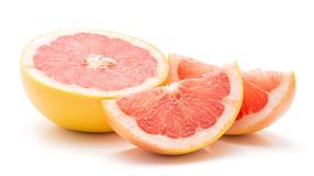 Red grapefruit isolated. Sliced red grapefruit isolated on white background one half and two slices Stock Images