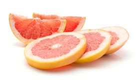 Red grapefruit isolated. Sliced red grapefruit isolated on white background three rings and two slices Royalty Free Stock Photos