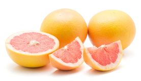 Red grapefruit isolated. On white background two whole one half and two slices Royalty Free Stock Image