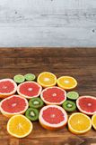 Red grapefruit, kiwi,  orange, and lime on wooden table. Vertica Stock Photo