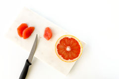 Red Grapefruit and Knife on Marble Chopping Board Royalty Free Stock Photography