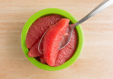 Red grapefruit sections in a green bowl with spoon Stock Photography