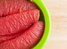 Red grapefruit sections in a green bowl top view Stock Photo