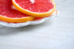 Red grapefruit slices on the plate Stock Images