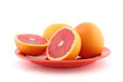 Red grapefruits. On orange plate royalty free stock image