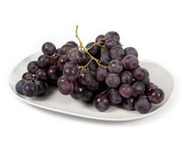 Red grapes. On a dish , isolated on white background Royalty Free Stock Images