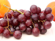 Red grapes. Some fresh red grapes on white background stock photos