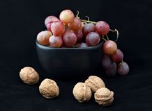 Red grapes in black bowl with walnuts. On black background stock image